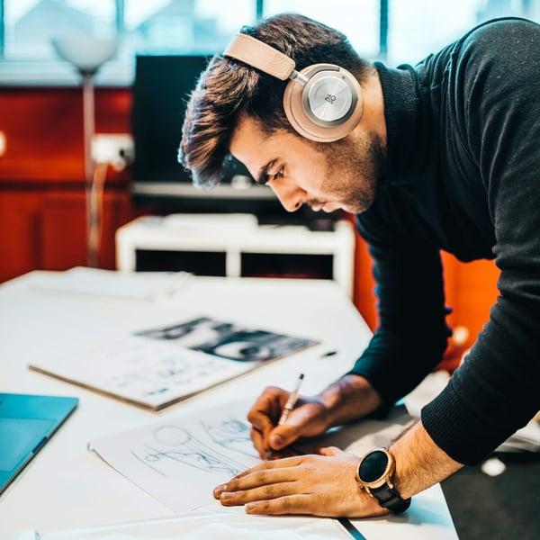 Man wearing headphones and sketching